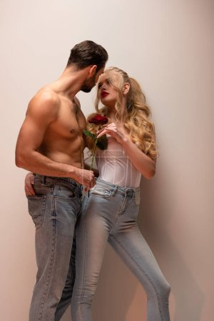 Photo for Shirtless man holding rose and looking at attractive girl on grey - Royalty Free Image