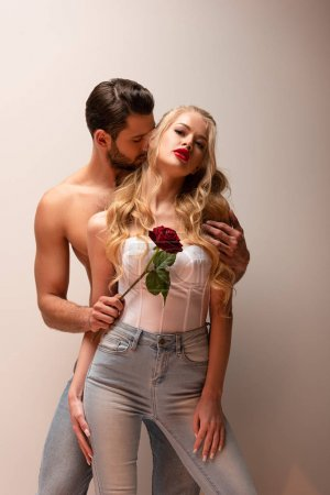 shirtless man holding rose and touching attractive girl on grey