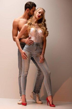 hemdloser Mann steht und berührt attraktives Mädchen auf grau