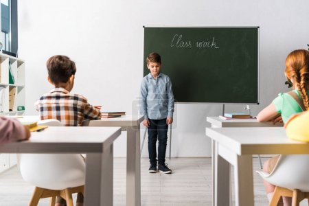 Photo for Schoolkids sitting at desks near classmate near chalkboard with class work lettering - Royalty Free Image