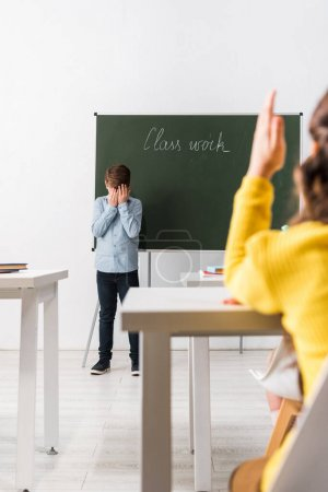 Photo for Selective focus of upset schoolboy covering face while standing near chalkboard and classmate with raised hand - Royalty Free Image