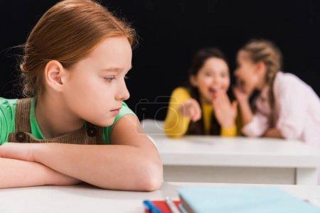 Photo pour Foyer sélectif d'écolier contrarié assis près de camarades de classe riant et bavardant dans la salle de classe isolé sur noir, concept d'intimidation - image libre de droit
