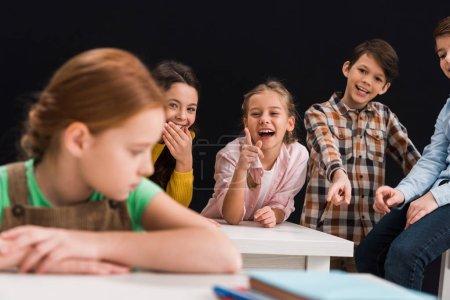 Photo pour L'accent sélectif des camarades de classe rire et pointer du doigt une écolière isolée sur le concept d'intimidation noire - image libre de droit