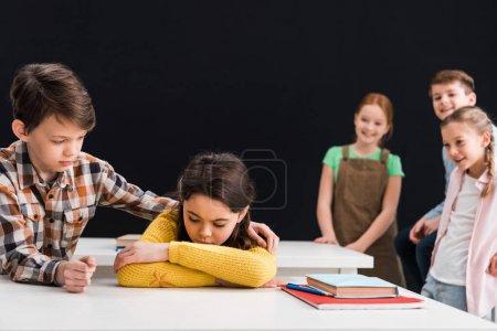 Photo pour Foyer sélectif de gentil écolier touchant bouleversé écolière près de souriants camarades de classe isolés sur noir, concept d'intimidation - image libre de droit