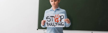 Photo for Panoramic shot of schoolboy holding placard with stop bullying lettering near chalkboard - Royalty Free Image