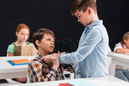 Foto de Enfoque selectivo del classmate de acoso escolar cerca de las niñas en edad escolar. - Imagen libre de derechos