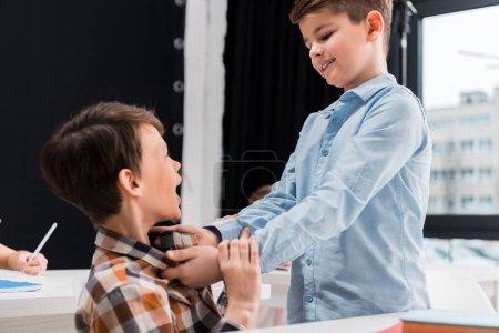Foto de Enfoque selectivo de sonrisas crueles en la escuela mientras se intimida a los compañeros de clase. - Imagen libre de derechos