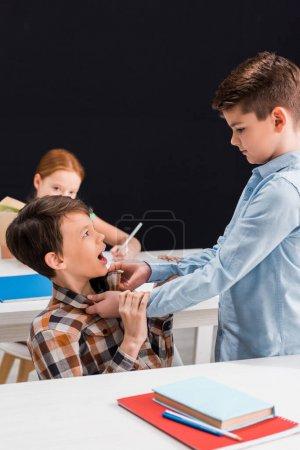Foto de Enfoque selectivo de la cruel clase de acoso escolar en la escuela aislada en negro. - Imagen libre de derechos