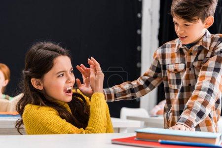 Foto de Enfoque selectivo de un niño de escuela cruel que abusa de una niña de escuela asustada en el aula. - Imagen libre de derechos