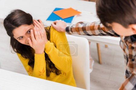 Foto de Enfoque selectivo de la cruel niña en edad escolar atemorizada en el aula. - Imagen libre de derechos