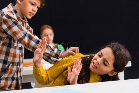 Foto de Enfoque selectivo de la cruel niña en edad escolar que intimida a una escuela atemorizada cerca de los compañeros de clase. - Imagen libre de derechos
