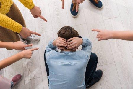 Foto de Visión superior de los niños de escuelas crueles que señalan con los dedos a los compañeros asfixiados. - Imagen libre de derechos