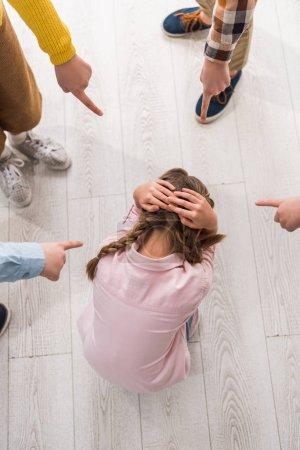 Foto de Visión superior de los niños de escuelas crueles que señalan con el dedo a las niñas escolarizadas acosadas. - Imagen libre de derechos
