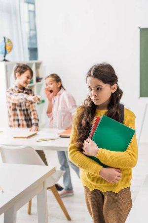 Foto de Enfoque selectivo de las niñas escolarizadas que tienen cuadernos cerca de compañeros crueles. - Imagen libre de derechos