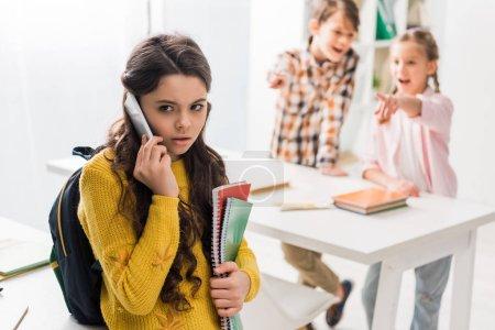 Foto de Enfoque selectivo de las niñas en edad escolar acosadas que hablan en teléfonos inteligentes cerca de compañeros crueles. - Imagen libre de derechos
