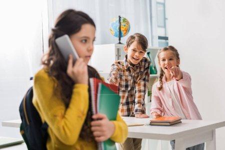 Foto de Enfoque selectivo de los compañeros de clase crueles señalando con el dedo a las niñas en edad escolar disgustadas hablando sobre teléfono inteligente, concepto de acoso. - Imagen libre de derechos