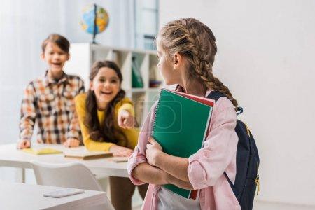 Photo pour Focalisation sélective des écolières intimidées tenant des cahiers près d'écolières cruelles - image libre de droit