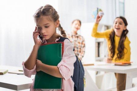 Foto de Enfoque selectivo de las niñas escolarizadas que hablan en teléfonos inteligentes cerca de los niños de escuelas crueles en el aula. - Imagen libre de derechos