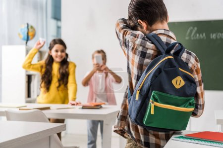 Photo for Back view of bullied kid standing near cruel classmates with smartphone, cyberbullying concept - Royalty Free Image