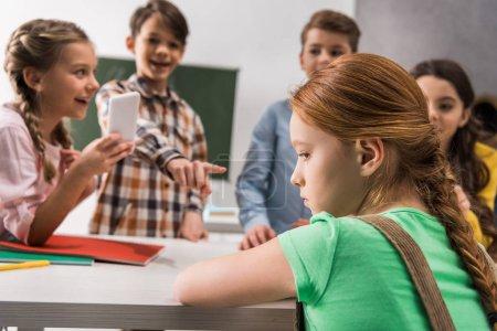 Photo pour Focalisation sélective d'une écolière déprimée assise près d'un écolier avec un téléphone intelligent et des camarades de classe cruels, concept de cyberintimidation - image libre de droit