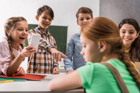 Photo pour Focalisation sélective des écoliers avec smartphone et camarades de classe cruels rire près d'un enfant victime d'intimidation, concept de cyberintimidation - image libre de droit