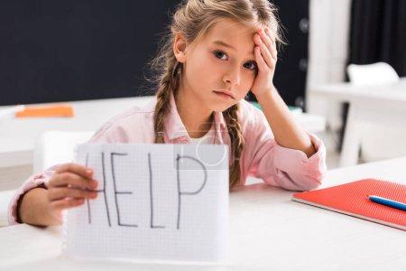Photo pour Focalisation sélective de triste écolière tenant du papier avec aide lettrage, concept d'intimidation - image libre de droit