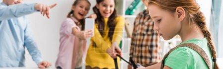 Photo pour Photo panoramique d'écolières intimidant une écolière en classe - image libre de droit