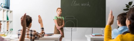 Photo for Panoramic shot of schoolkgirl standing near chalkboard with class work lettering and classmates with raised hands - Royalty Free Image