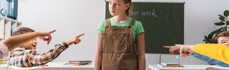 Photo pour Plan panoramique de camarades de classe cruels pointant du doigt une écolière brutalisée en classe - image libre de droit