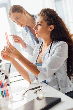 Photo pour Foyer sélectif des infirmières attrayantes et sexy regardant le tube à essai avec du liquide - image libre de droit