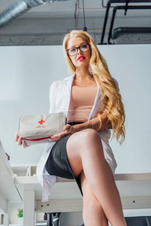 Photo pour Low angle view of sexy nurse in glasses holding first aid kit - image libre de droit