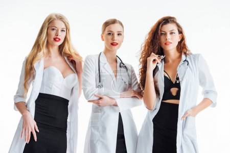 Photo pour Sexy nurses in white coats posing isolated on white - image libre de droit