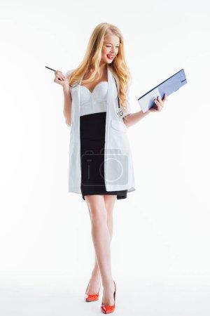 Photo pour Infirmière gaie et sexy regardant presse-papiers et tenant stylo sur blanc - image libre de droit
