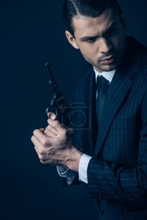 Photo for Gangster holding weapon with clenched hands on dark blue - Royalty Free Image