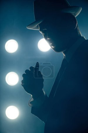 Photo for Silhouette of mafioso holding cigar and looking at camera on dark background - Royalty Free Image