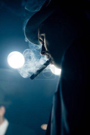 Photo for Low angle view of mafioso smoking cigar on dark - Royalty Free Image