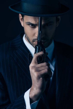 Photo for Gangster holding gun in front of face on dark blue - Royalty Free Image