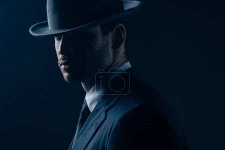 Photo for Portrait of mafioso in felt hat and suit on dark blue background - Royalty Free Image