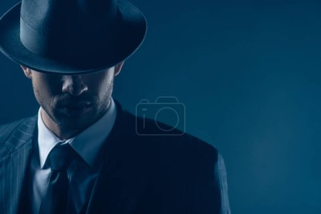 Photo for Portrait of mafioso with covered eyes with felt hat on dark - Royalty Free Image