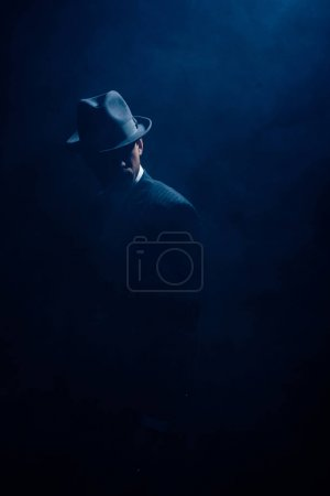 Photo for Silhouette of mafioso in suit and felt hat on dark blue background - Royalty Free Image