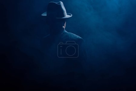 Photo pour Silhouette de mafioso en feutre chapeau et costume sur fond sombre - image libre de droit