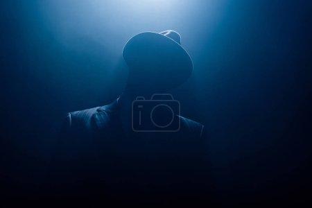 Photo pour Silhouette de gangster dangereux en costume et chapeau en feutre sur fond sombre - image libre de droit