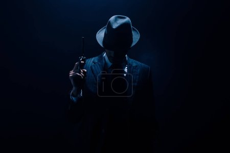 Photo pour Silhouette of gangster raising gun on dark blue background - image libre de droit