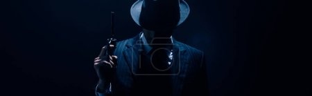 Photo pour Silhouette of gangster raising gun on dark blue background, panoramic shot - image libre de droit