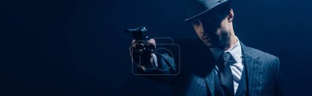 Photo pour Gangster aiming weapon with outstretched hand on dark background, panoramic shot - image libre de droit