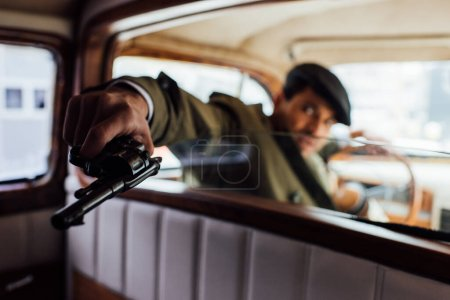 Photo for Selective focus of dangerous gangster aiming revolver in car - Royalty Free Image