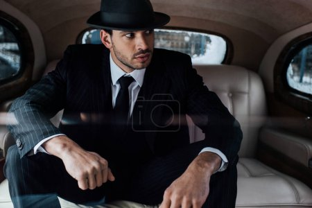 Photo for Selective focus of tense mafioso in black suit and felt hat in retro car - Royalty Free Image