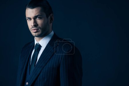 Elegant mafioso looking at camera on dark blue background
