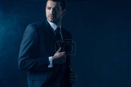 Confident mafioso looking away on dark blue background