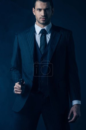 Front view of confident gangster aiming weapon and looking at camera on dark blue background
